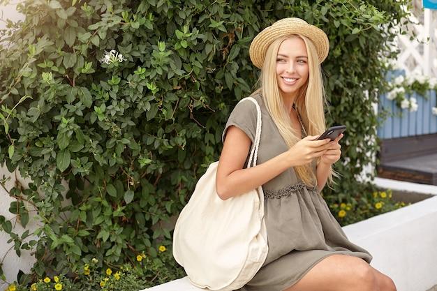 Foto ao ar livre de uma jovem loira bonita com o celular nas mãos, vestindo roupas casuais e chapéu de palha, olhando para o lado com um sorriso encantador
