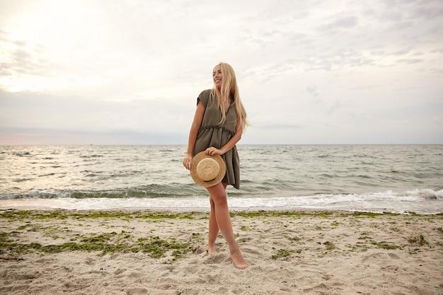 Foto ao ar livre de uma jovem loira de cabelos compridos, magro, com um vestido romântico de verão, olhando alegremente para o lado enquanto posava à beira-mar com um chapéu de palha