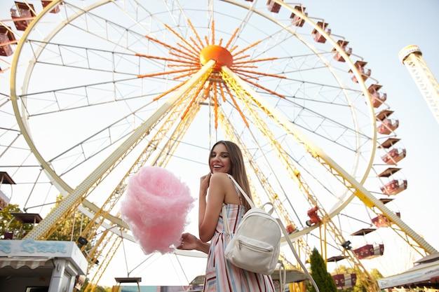 Foto ao ar livre de uma jovem morena feliz com cabelo comprido, usando um vestido romântico e uma mochila branca, em pé sobre a roda gigante em um dia quente de verão, segurando um algodão doce e sorrindo amplamente