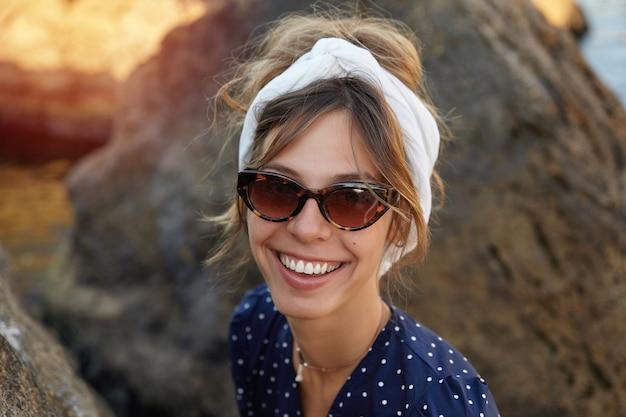 Foto ao ar livre de uma jovem mulher alegre com óculos vintage, vestido romântico, parecendo com um sorriso largo e feliz, posando à beira-mar num dia de verão
