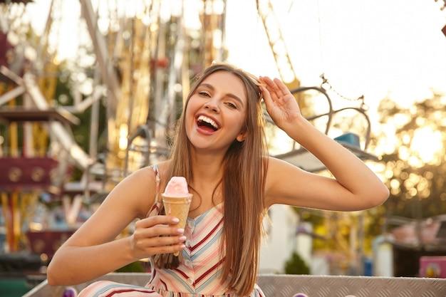 Foto ao ar livre de uma jovem mulher feliz com cabelo comprido, tomando sorvete no cone enquanto caminhava pelo parque de diversões, rindo alegremente com a boca aberta e tirando os óculos de sol