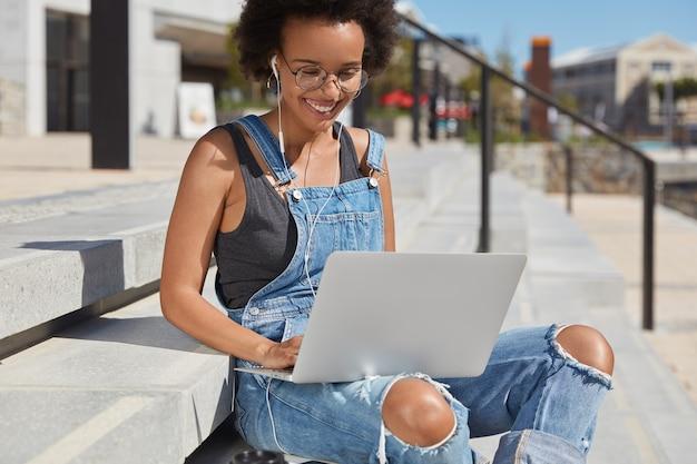Foto ao ar livre de uma jovem negra satisfeita em um macacão esfarrapado da moda, faz videochamada, usa um laptop moderno e fones de ouvido, senta-se na escada, ouve um livro de áudio, sorri positivamente.