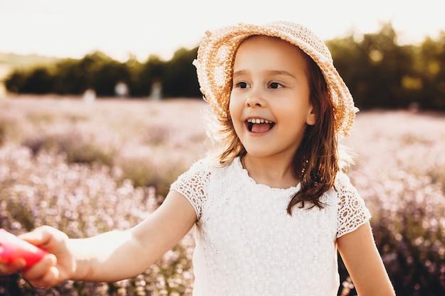 Foto ao ar livre de uma linda criança sorrindo enquanto joga contra o pôr do sol. linda garota pequena brincando e rindo ao fazer balões de sabão em um campo de flores.