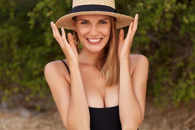 Foto ao ar livre de uma linda mulher encantada com chapéu de verão relaxa arquibancadas do lado de fora contra plantas verdes, parece com um largo sorriso, feliz por passar o feriado junto com o namorado.