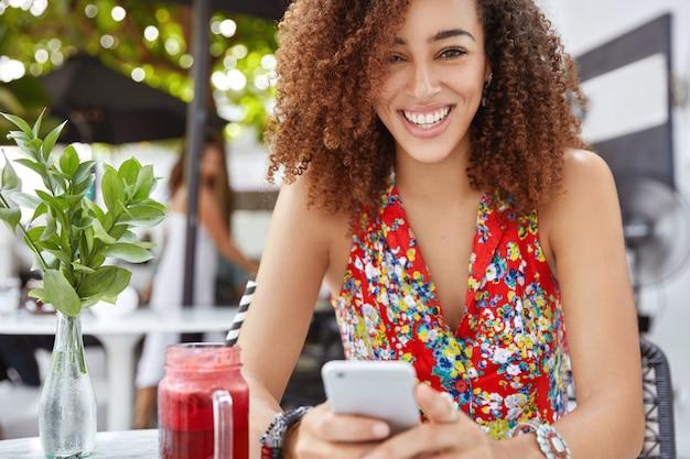 Foto ao ar livre de uma linda mulher encaracolada com pele escura, lê notícias agradáveis ou pesquisa informações em redes sociais