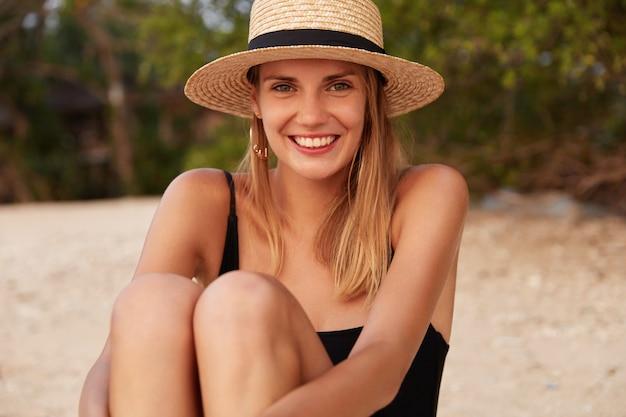 Foto ao ar livre de uma linda mulher usando chapéu de palha e maiô, sentada na quente praia de areia, satisfeita com as condições climáticas e bom descanso, se sente feliz e relaxada. mulher sozinha na praia