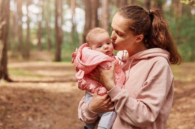 Foto ao ar livre de uma mãe jovem e amorosa, segurando a garotinha nas mãos e beijando-a