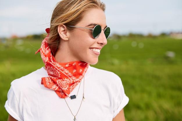 Foto ao ar livre de uma motociclista alegre usando óculos escuros elegantes e bandana, aprecia a liberdade enquanto caminha pelo campo verde calmo, admira as maravilhosas paisagens naturais.