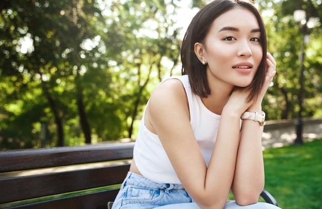Foto ao ar livre de uma mulher asiática descansando no parque, sentada no banco e olhando um sonho para a câmera