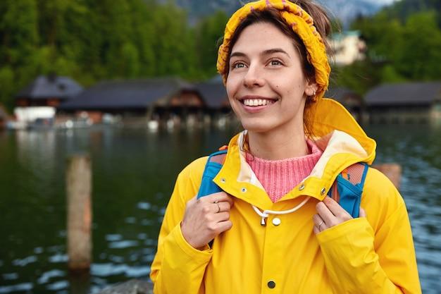 Foto ao ar livre de uma mulher caucasiana gosta de explorar o ambiente
