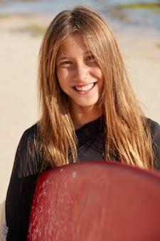 Foto ao ar livre de uma mulher de cabelos claros com aparência agradável, sorriso cheio de dentes, expressão agradável, usa roupa de mergulho, segura uma prancha de surf