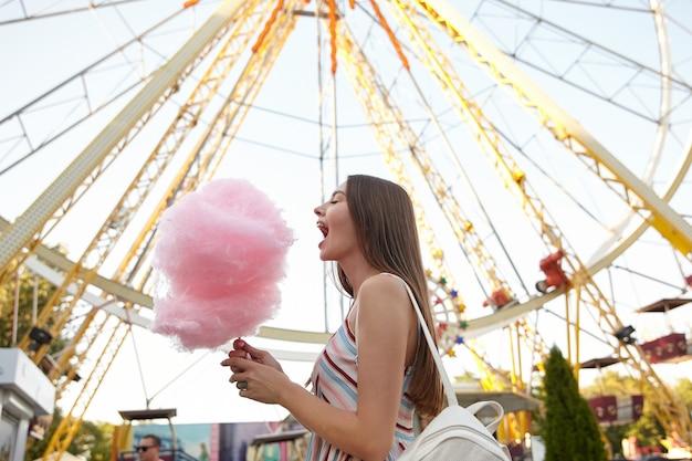 Foto ao ar livre de uma mulher de cabelos compridos em um vestido leve e mochila branca posando sobre a roda gigante, em pé com a boca aberta e indo comer algodão doce