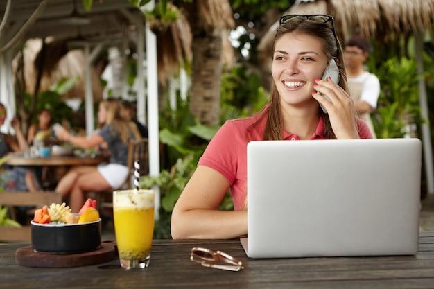 Foto ao ar livre de uma mulher de negócios atraente e alegre com óculos na cabeça, sentada em um restaurante na calçada