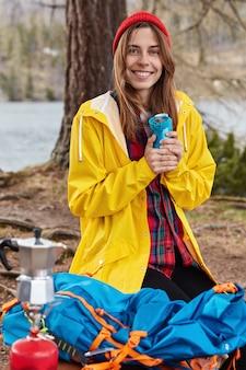 Foto ao ar livre de uma mulher europeia com uma expressão alegre, ajoelhada no chão em uma floresta perto do rio