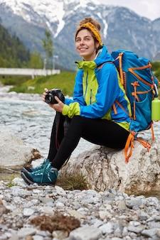 Foto ao ar livre de uma mulher feliz descansando enquanto está sentada em uma pedra perto de um pequeno rio na montanha, segurando uma câmera profissional para tirar fotos