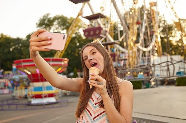 Foto ao ar livre de uma mulher jovem e atraente com cabelo castanho comprido fazendo selfie com seu smartphone sobre a roda gigante, usando um vestido leve de verão e óculos escuros, lambendo o sorvete e fechando um olho