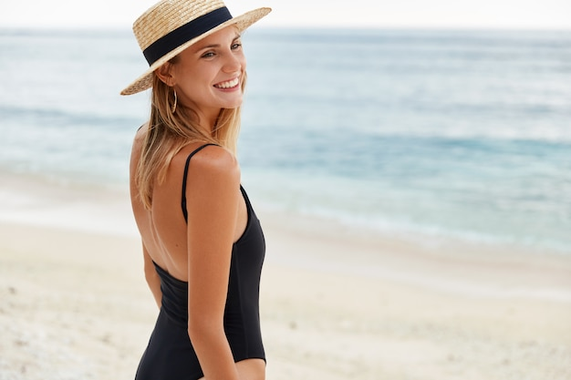 Foto ao ar livre de uma mulher satisfeita com a pele queimada pelo sol, usa chapéu de palha e maiô, caminha pela costa, desfruta de bom descanso à beira-mar, olha feliz para os amigos. pessoas e férias de verão