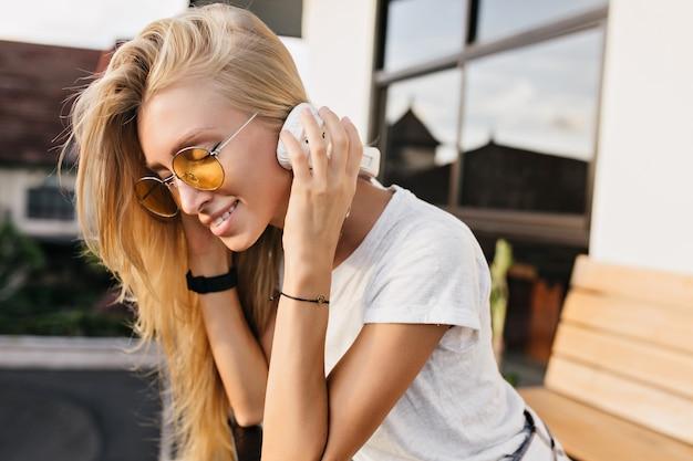 Foto ao ar livre de uma romântica garota caucasiana em óculos de sol amarelos, sorrindo enquanto ouve música.