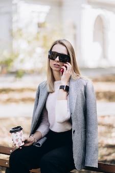 Foto ao ar livre de uma senhora loira com café sentado no banco em dia de outono. estilo de moda de rua. vestindo calças escuras casuais, suéter creme e óculos escuros conceito de moda e descanso.