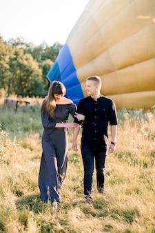 Foto ao ar livre de verão de um jovem casal alegre caminhando durante o pôr do sol em campo verde, posando para a câmera na frente de um balão de ar quente amarelo, preparando-se para o voo