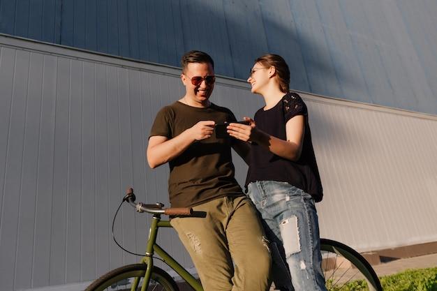 Foto ao ar livre do jovem casal atraente, rindo juntos durante assistir algo engraçado no celular, passar tempo com prazer, em pé com a bicicleta.