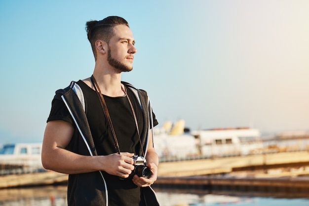 Foto ao ar livre do jovem fotógrafo masculino bonito em pé no porto, olhando como o pôr do sol se reflete no mar e nas ondas, sonhando ou inventando a idéia de tirar foto de belas paisagens com a câmera