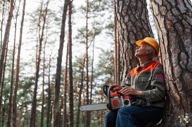 Foto ao ar livre do lenhador descansando ao ar livre após o corte de árvores