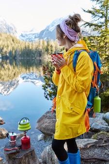Foto ao ar livre vertical de hicker feminina pensativa segurando uma bebida quente em uma xícara de chá, fazendo a bebida em equipamento turístico especial