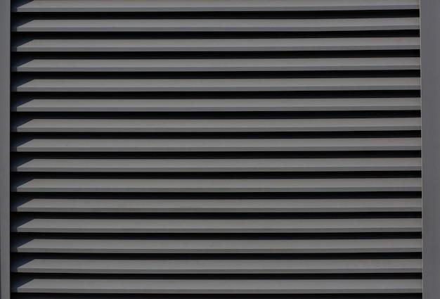 Foto aproximada ao ar livre de persianas de metal com sombras