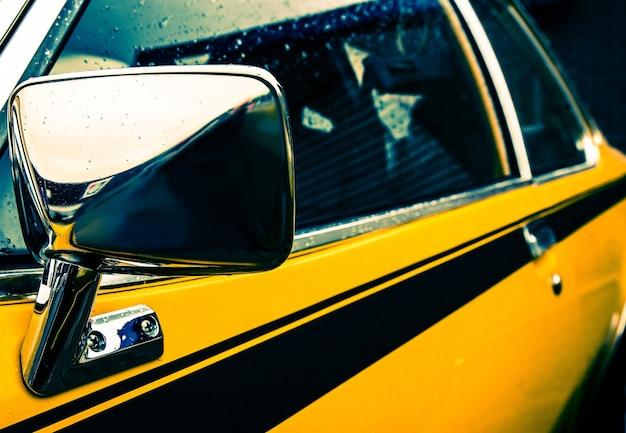 Foto aproximada da lateral de um carro amarelo com uma linha preta sob as janelas