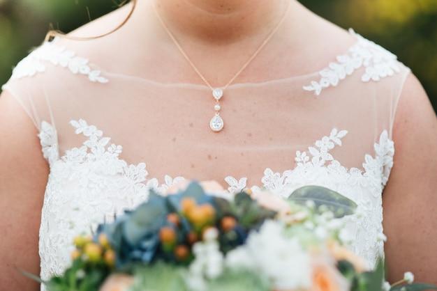 Foto aproximada da noiva em um vestido de noiva segurando o buquê