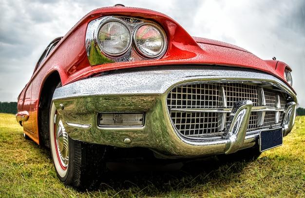 Foto aproximada da parte dianteira de um carro vermelho estacionado em um campo verde