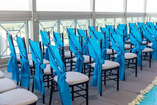 Foto aproximada das elegantes cadeiras azuis no local do casamento