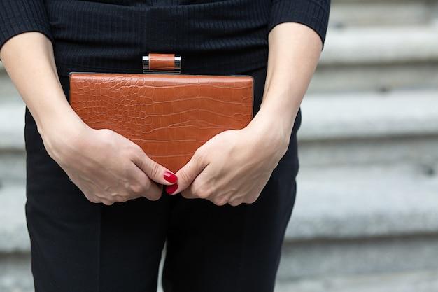 Foto aproximada das mãos de uma mulher segurando uma bolsa de couro marrom