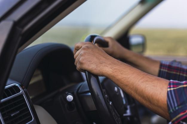 Foto aproximada das mãos de uma pessoa no volante de um carro moderno