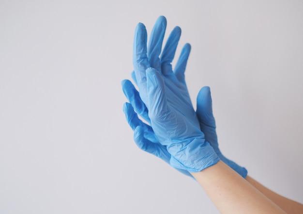 Foto aproximada das mãos de uma pessoa usando luvas azuis