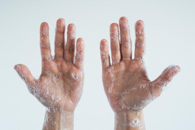 Foto aproximada das mãos ensaboadas de uma pessoa