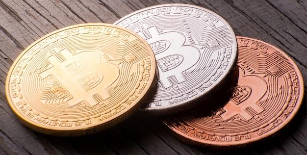 Foto aproximada de bitcoin de ouro, prata e bronze em uma superfície de madeira