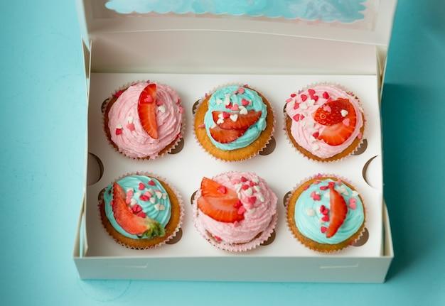 Foto aproximada de cupcakes coloridos com morango