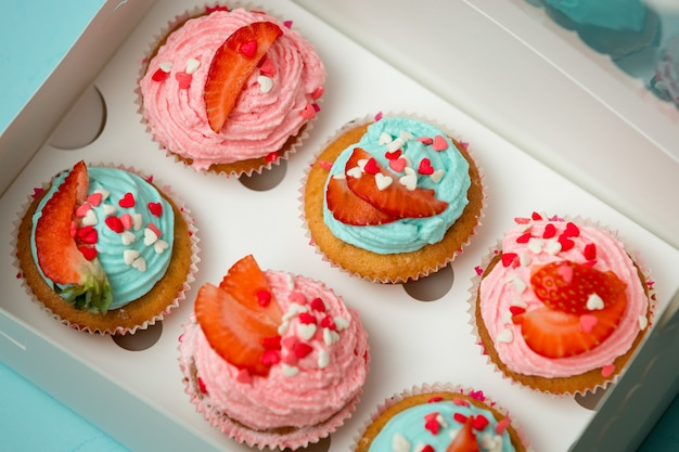 Foto aproximada de cupcakes decorados na caixa