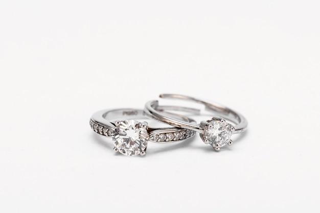 Foto aproximada de dois anéis de diamante em uma superfície branca
