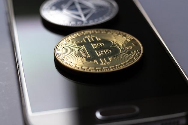 Foto aproximada de duas moedas colocadas em cima de um telefone celular