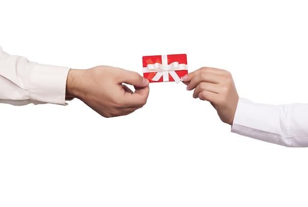 Foto aproximada de duas pessoas segurando um cartão-presente vermelho sobre um fundo branco