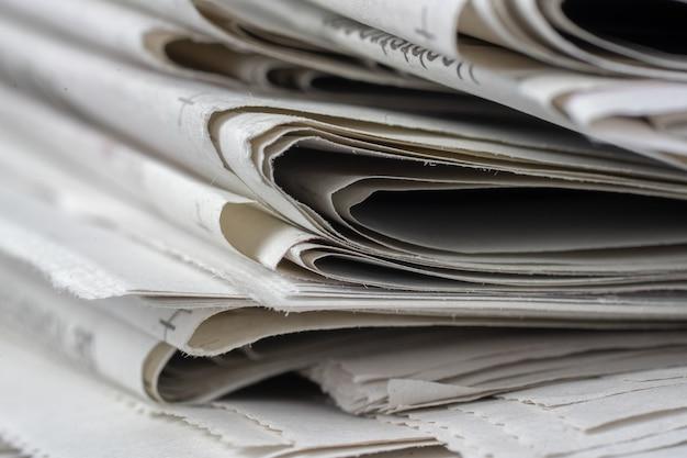 Foto aproximada de jornais empilhados uns em cima dos outros