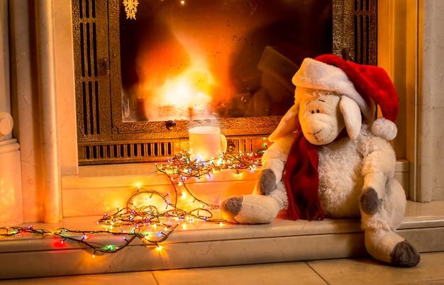 Foto aproximada de ovelhas de brinquedo sentadas ao lado da lareira no ano novo