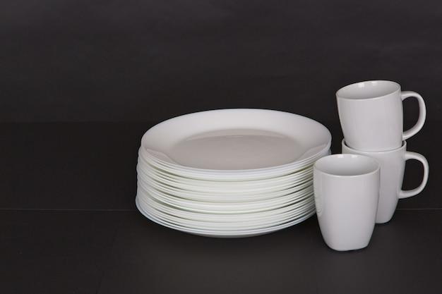 Foto aproximada de pratos e canecas brancos em um fundo preto