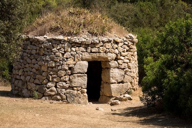 Foto aproximada de um antigo abrigo de pedra em uma floresta