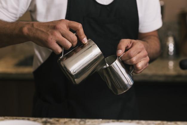Foto aproximada de um barista fazendo arte com café com leite em uma cafeteria