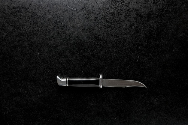 Foto aproximada de um canivete com cabo preto