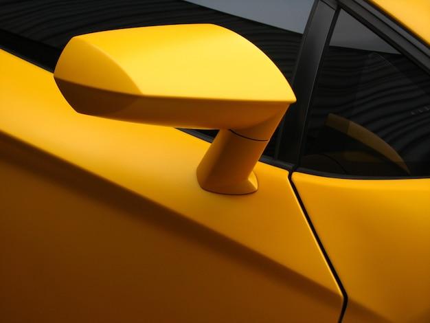 Foto aproximada de um carro esporte amarelo